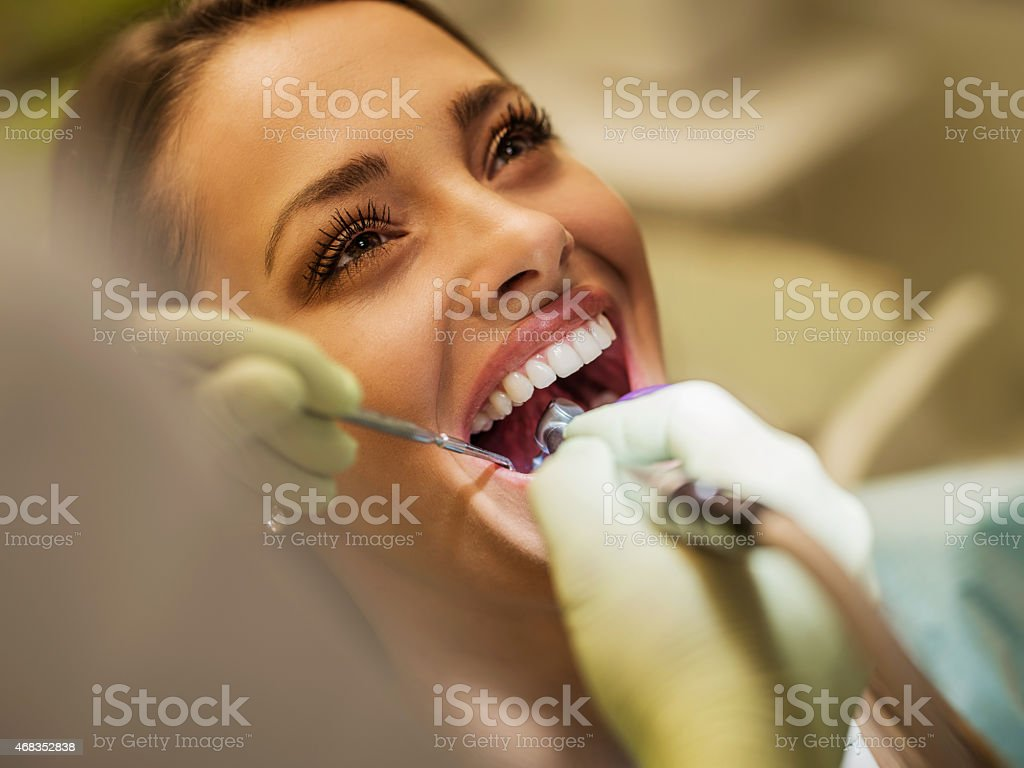 Close up of a happy woman visiting dentist. stock photo
