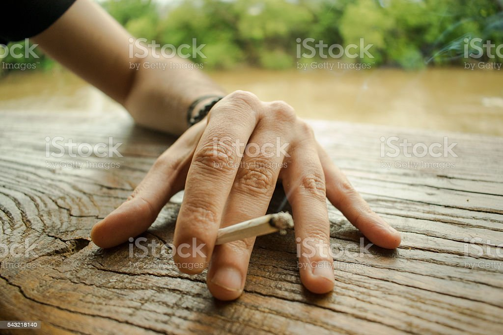 Close up of a human hand holding rolled up joint stock photo
