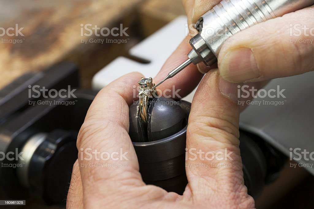 Close up of a jeweler's hands doing a repair stock photo