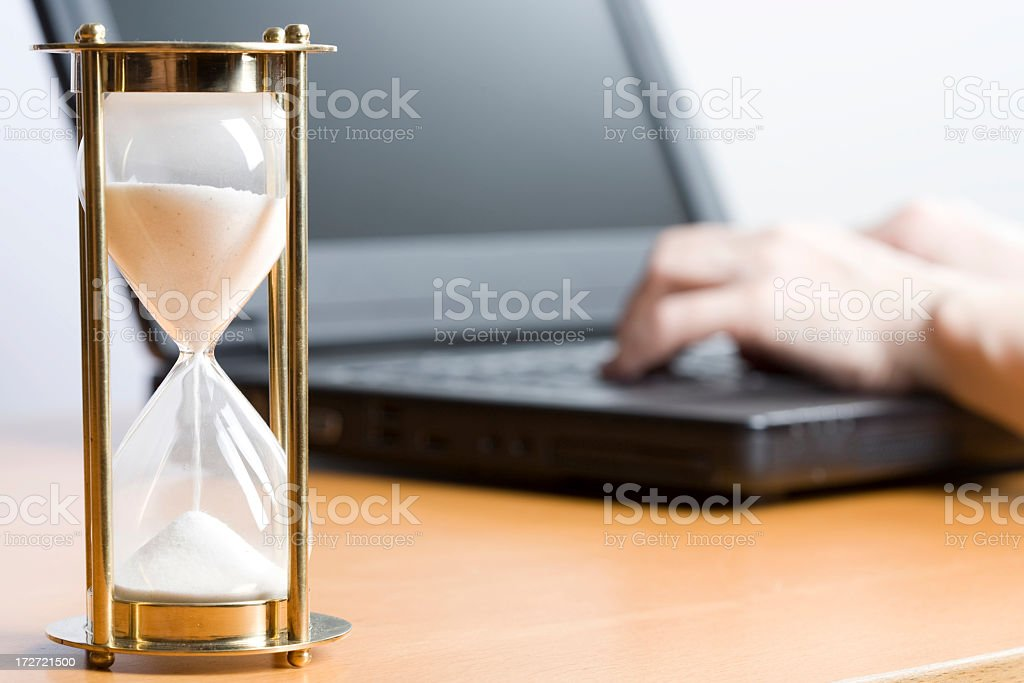 Close up of a large egg timer and a person working on laptop royalty-free stock photo