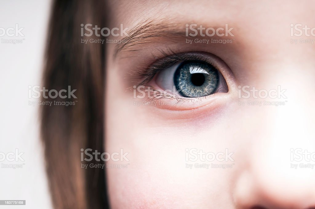 A close up of a little girl's blue eye stock photo