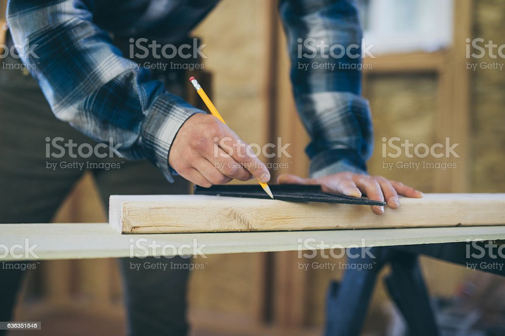 Close up of a males hands using a square and pencil stock photo
