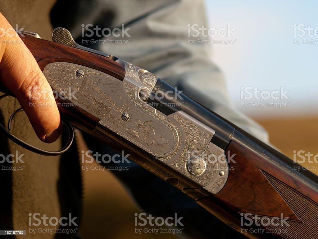 A close up of a man holding a shotgun stock photo