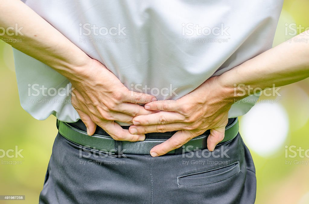 close up of a  man holding his back in pain. stock photo