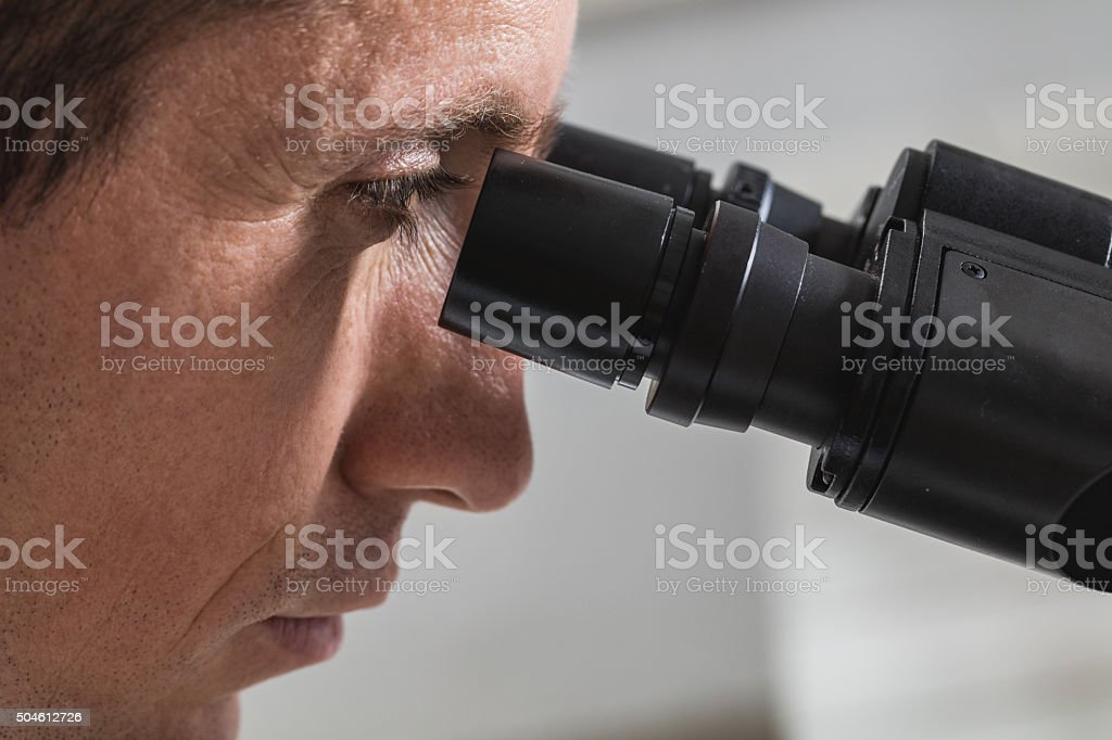 Close up of a man looking through a microscope. stock photo