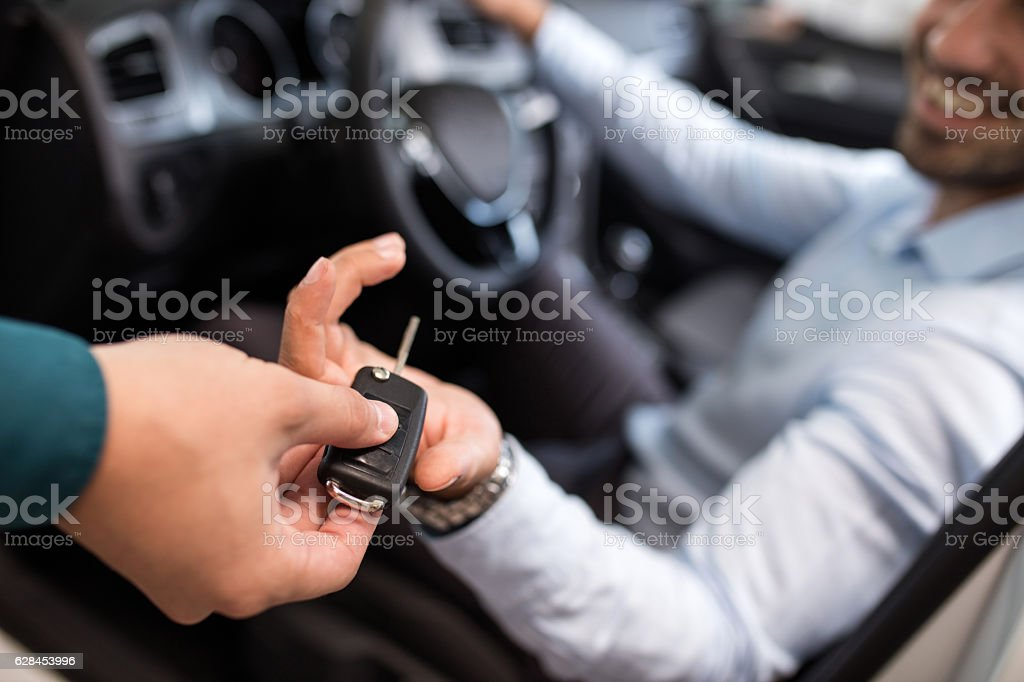Close up of a man receiving new car key. stock photo