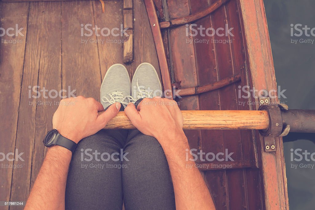 Close up of a man rowing in a wooden boat. stock photo