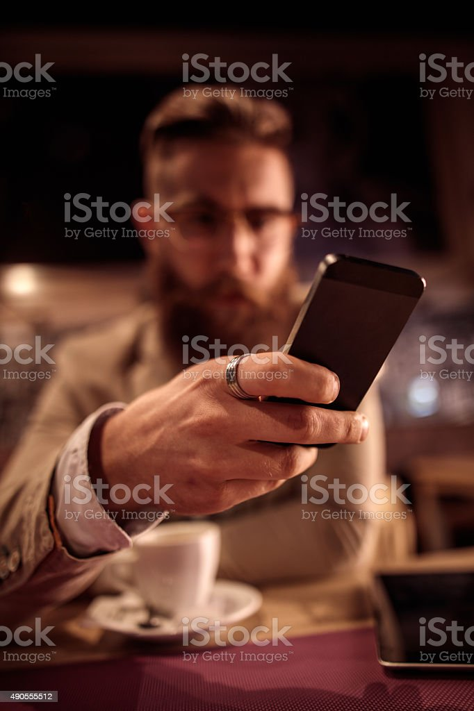 Close up of a man text messaging on smart phone. stock photo