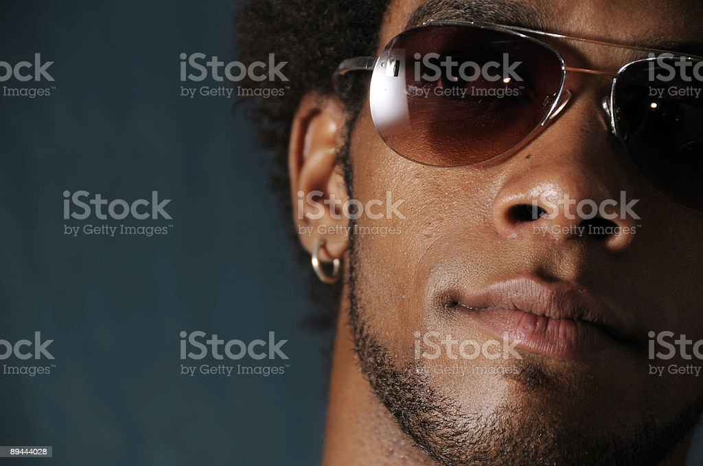 Close up of a man's face wearing sunglasses and earrings royalty-free stock photo