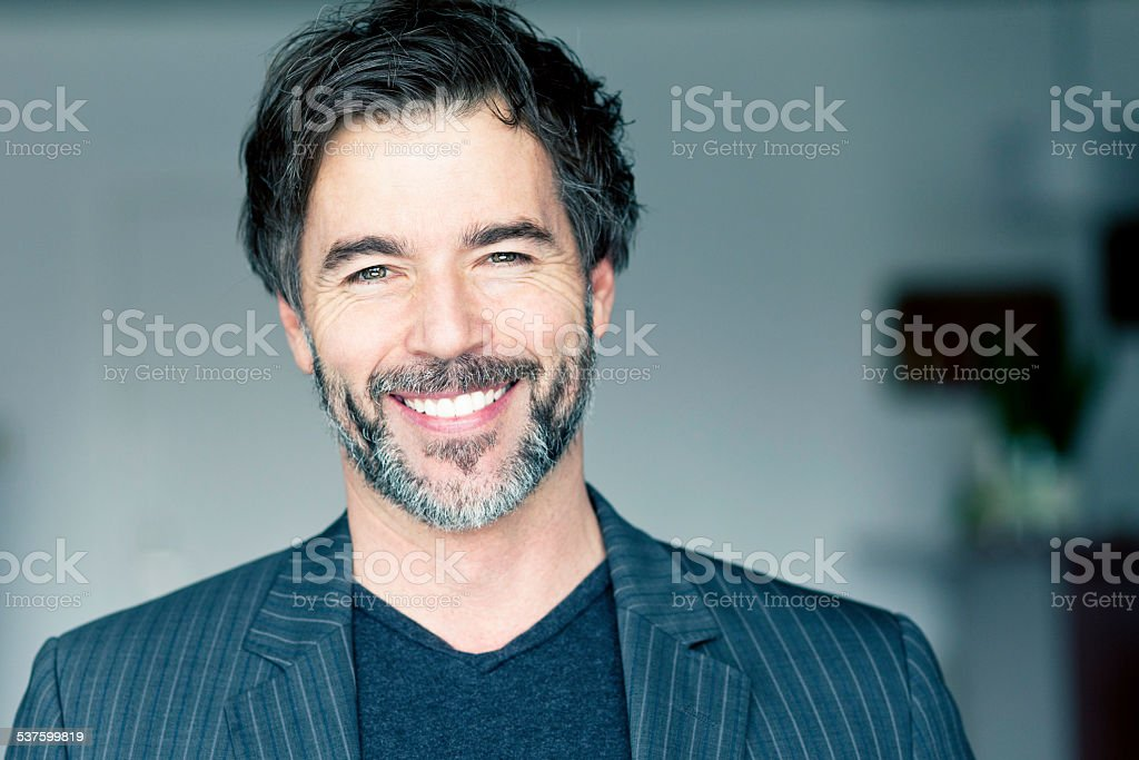 Close Up Of A Mature Man Smiling At The Camera stock photo