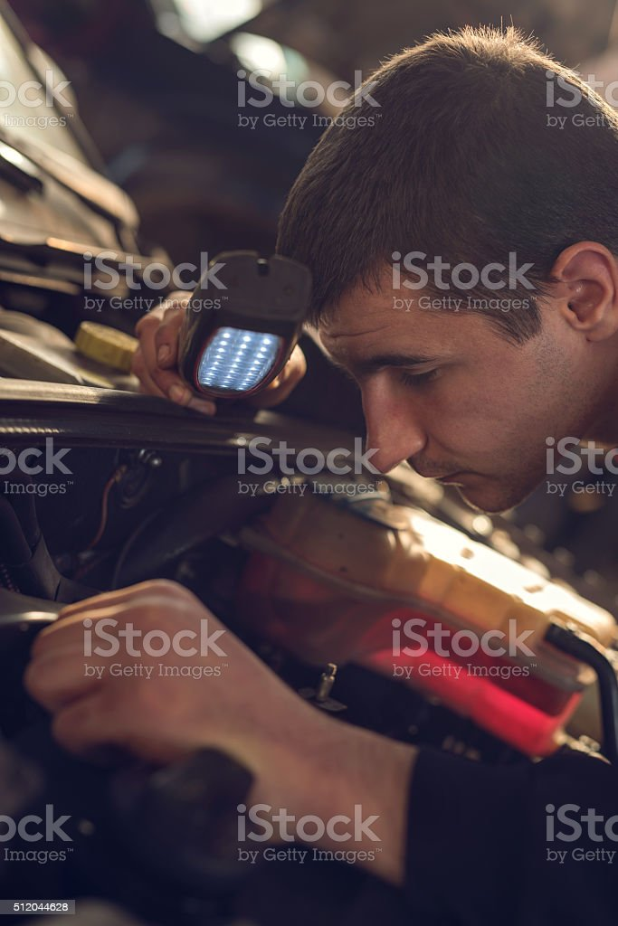 Close up of a mechanic examining an engine. stock photo