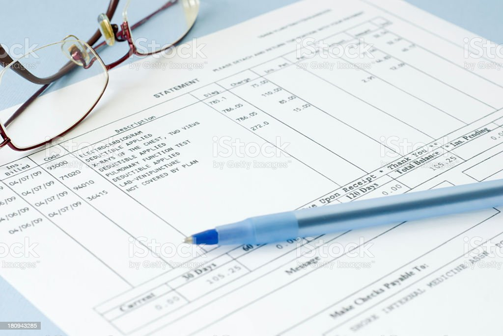 Close up of a medical bill featuring glasses and a pen  stock photo