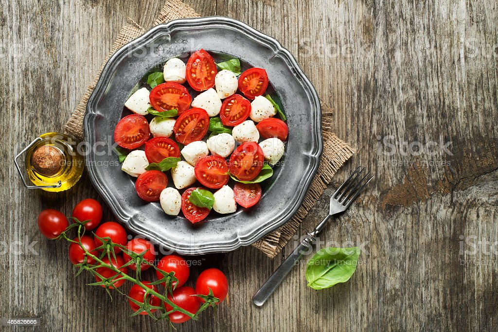 Close up of a mozzarella tomato salad with basil stock photo