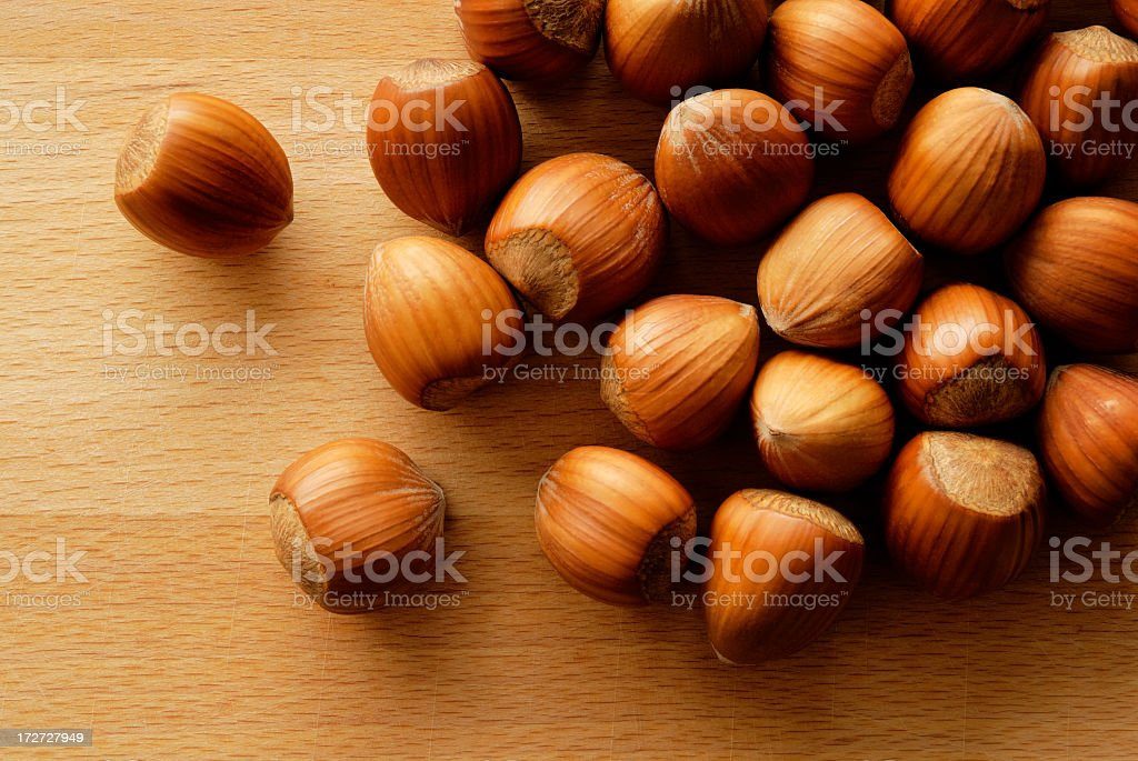 Close up of a pile of hazelnuts on a wood table royalty-free stock photo