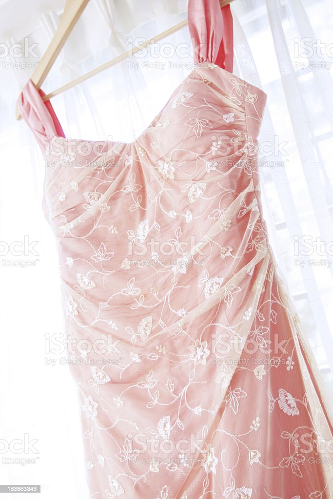 Close up of a pink wedding dress hanging on window stock photo