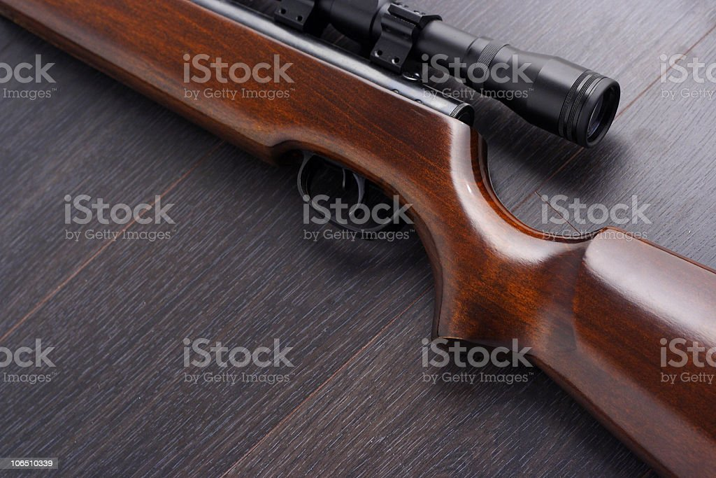 Close up of a rifle with smooth wooden butt royalty-free stock photo