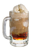 A close up of a root beer float in a glass mug