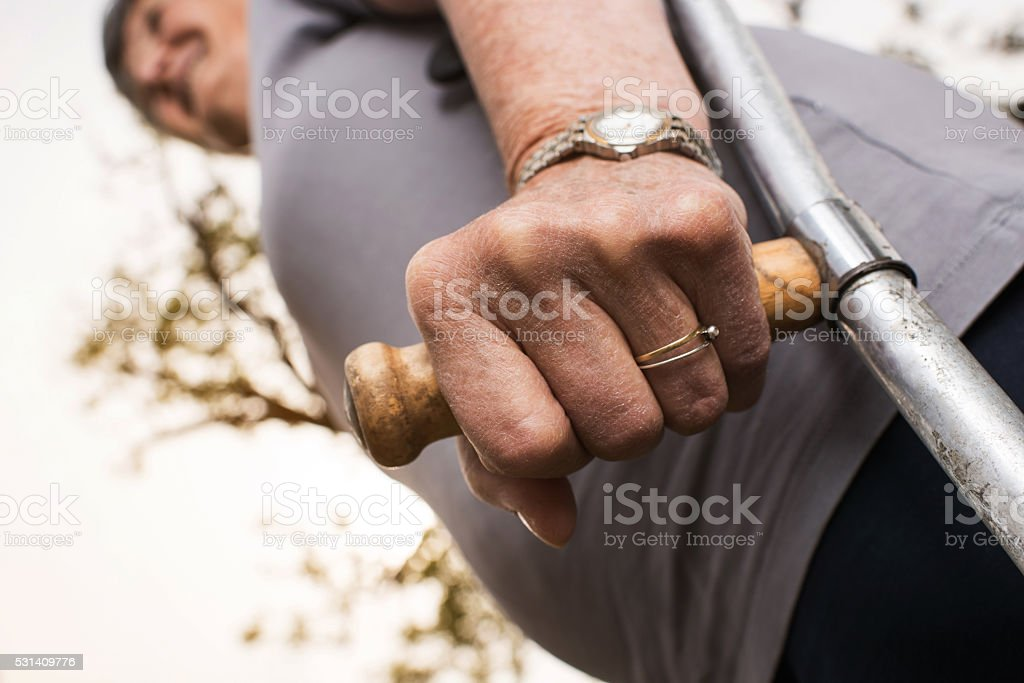 Close up of a senior person on a crutch outdoors. stock photo