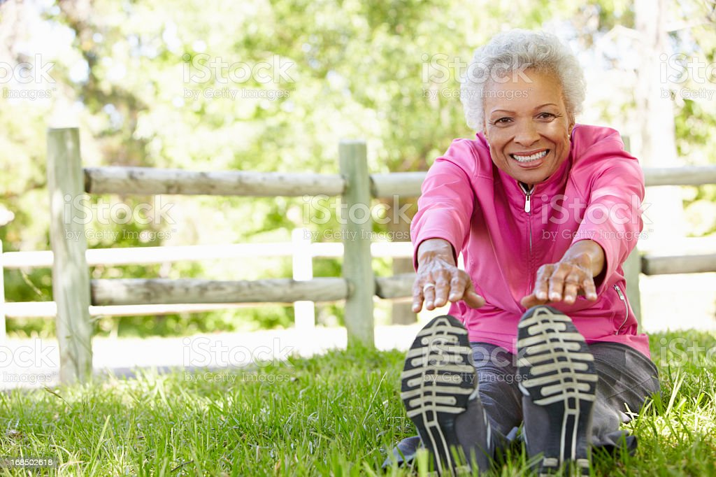 Close up of a senior woman stretching in the park  stock photo