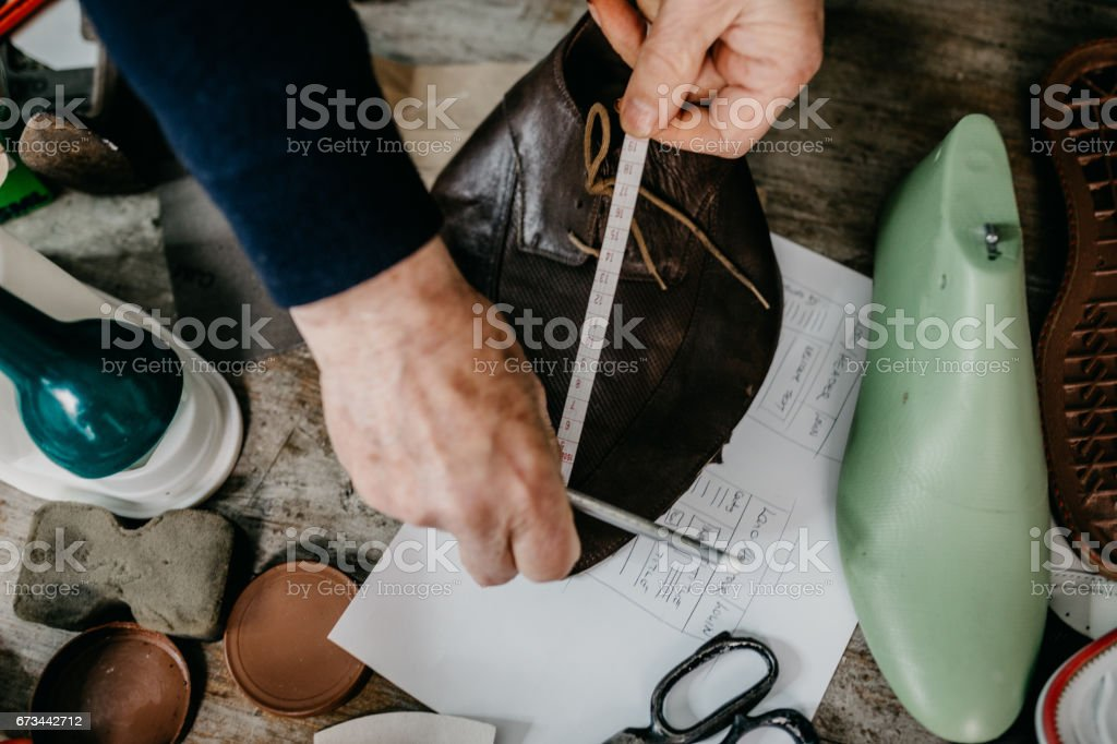 Close up of a shoemaker taking measurements for making a shoe stock photo