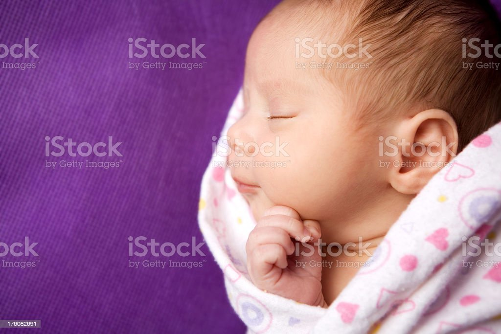 Close up of a sleeping, swaddled, newborn baby girl stock photo