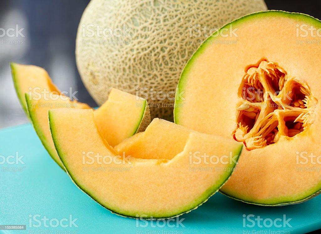 A close up of a sliced cantaloupe on a blue table stock photo