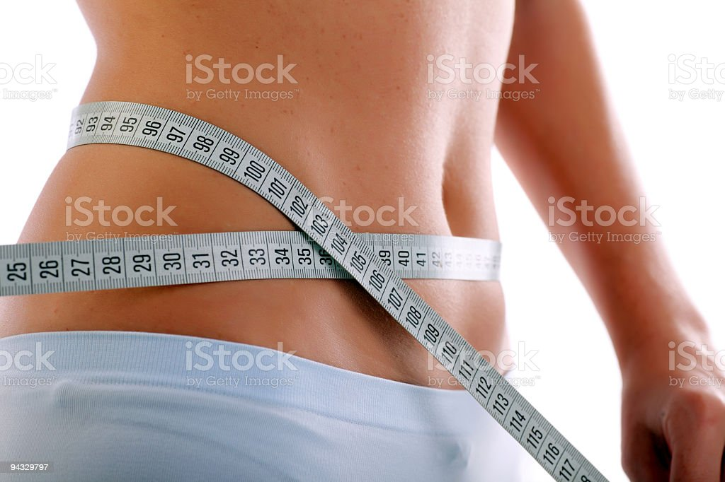 Close up of a slim waist with measuring tape. stock photo