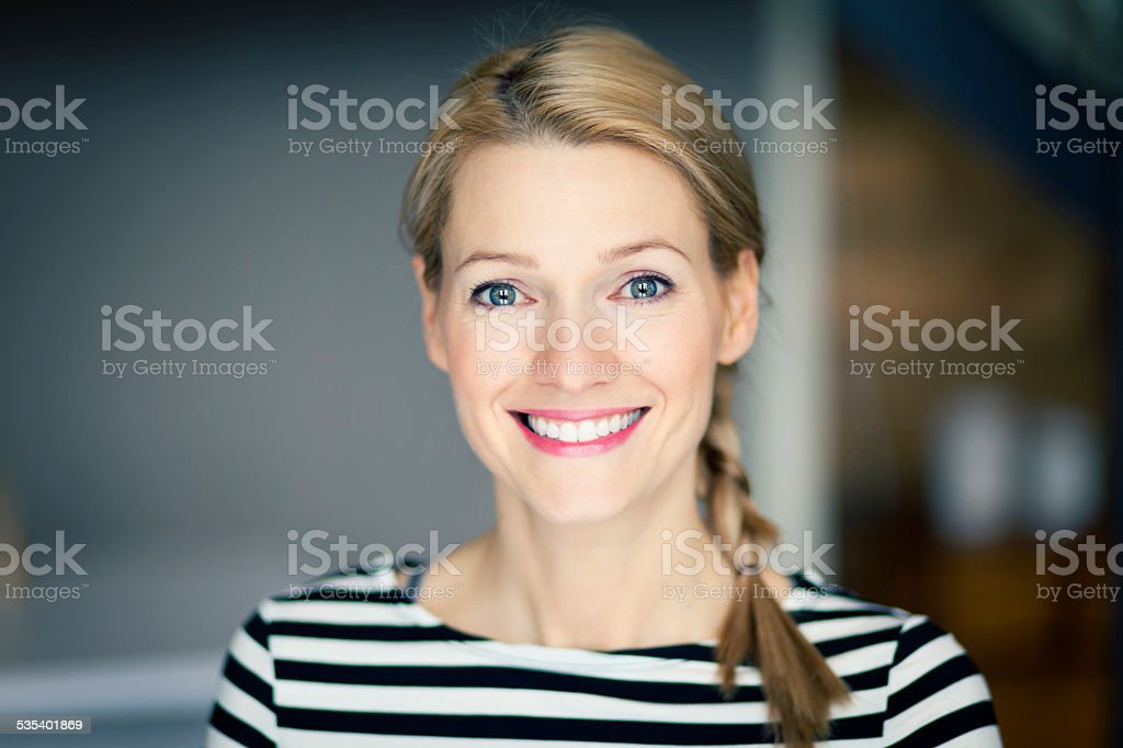 Close up Of A Smiling blond woman wearing a striped shirt stock photo
