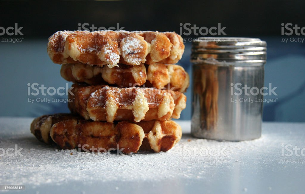 Close up of a stack of waffles with an icing sugar shaker stock photo