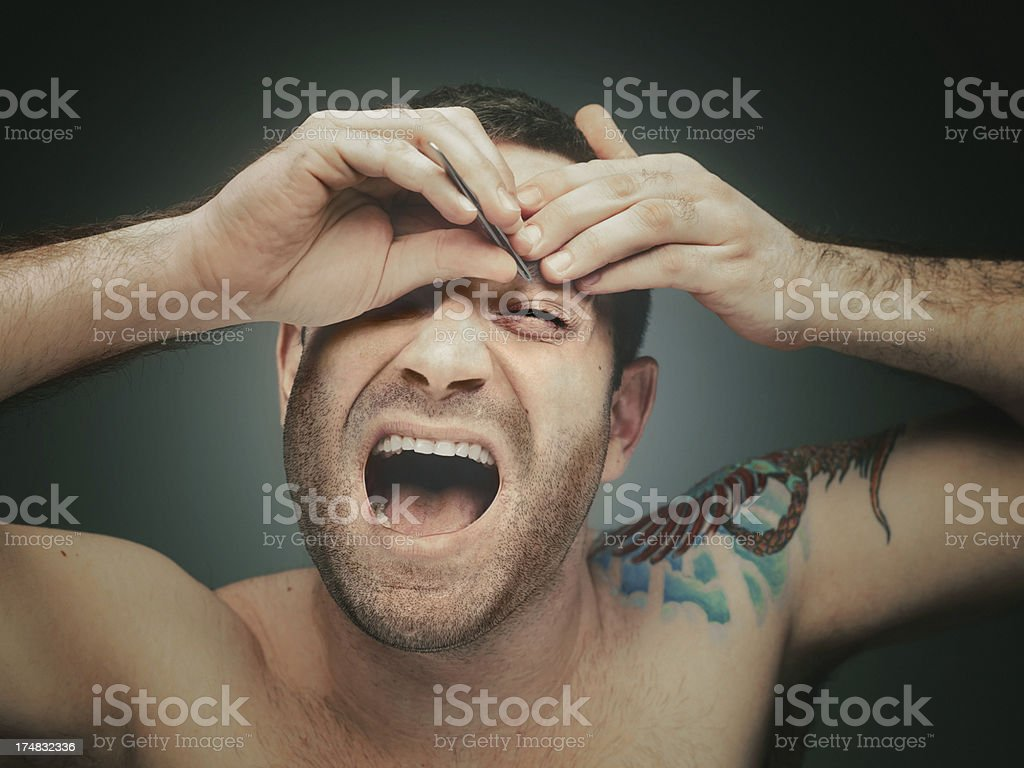 Close up of a tattoed man plucking eyebrows royalty-free stock photo