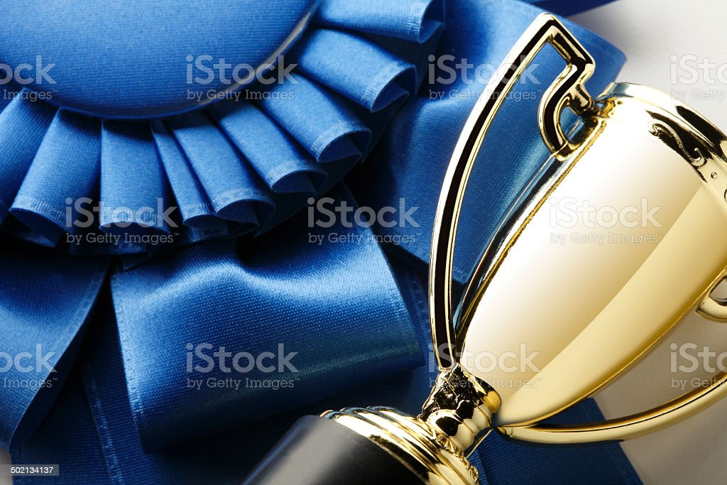 Close up of a trophy and a blue ribbon stock photo