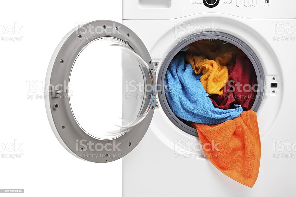 Close up of a washing machine loaded with clothes stock photo