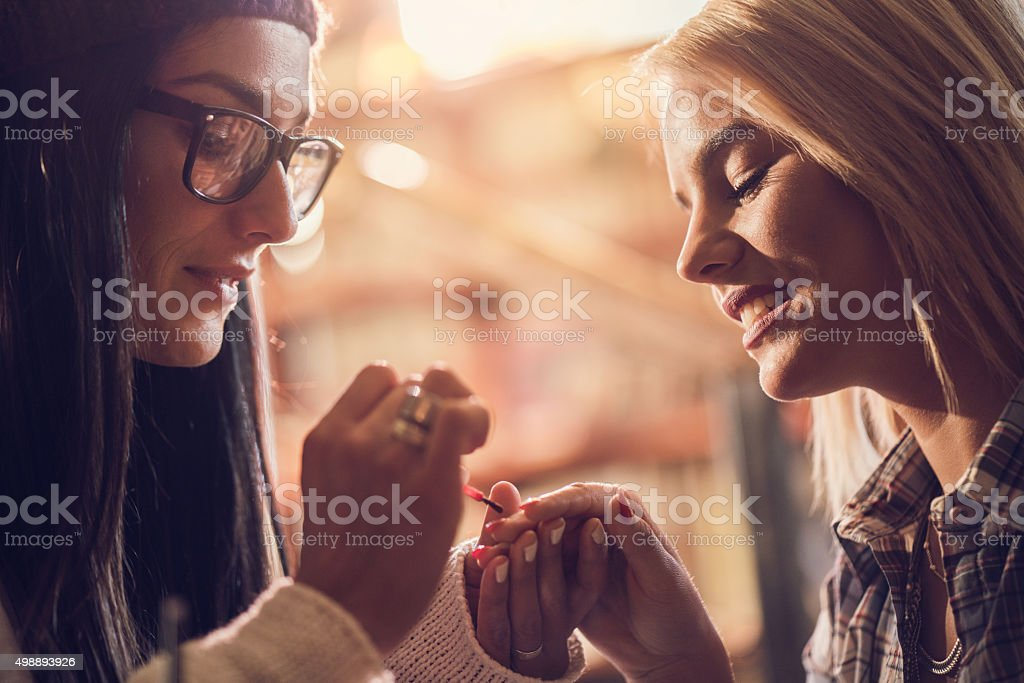 Close up of a woman painting her friend's nails. stock photo