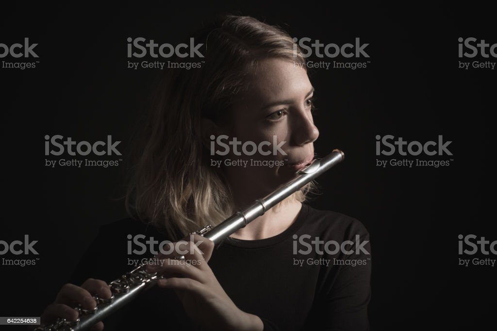 Close Up of a Woman Playing a Flute stock photo