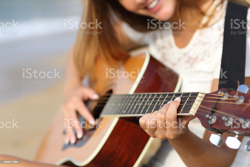 Close up of a woman playing guitar on the beach stock photo