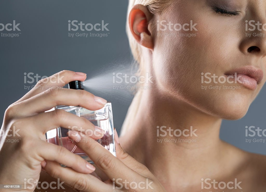 Close up of a woman spraying perfume on her neck. stock photo