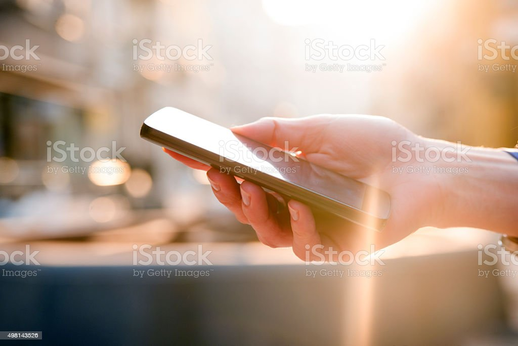 Close up of a woman using mobile smart phone outdoor stock photo