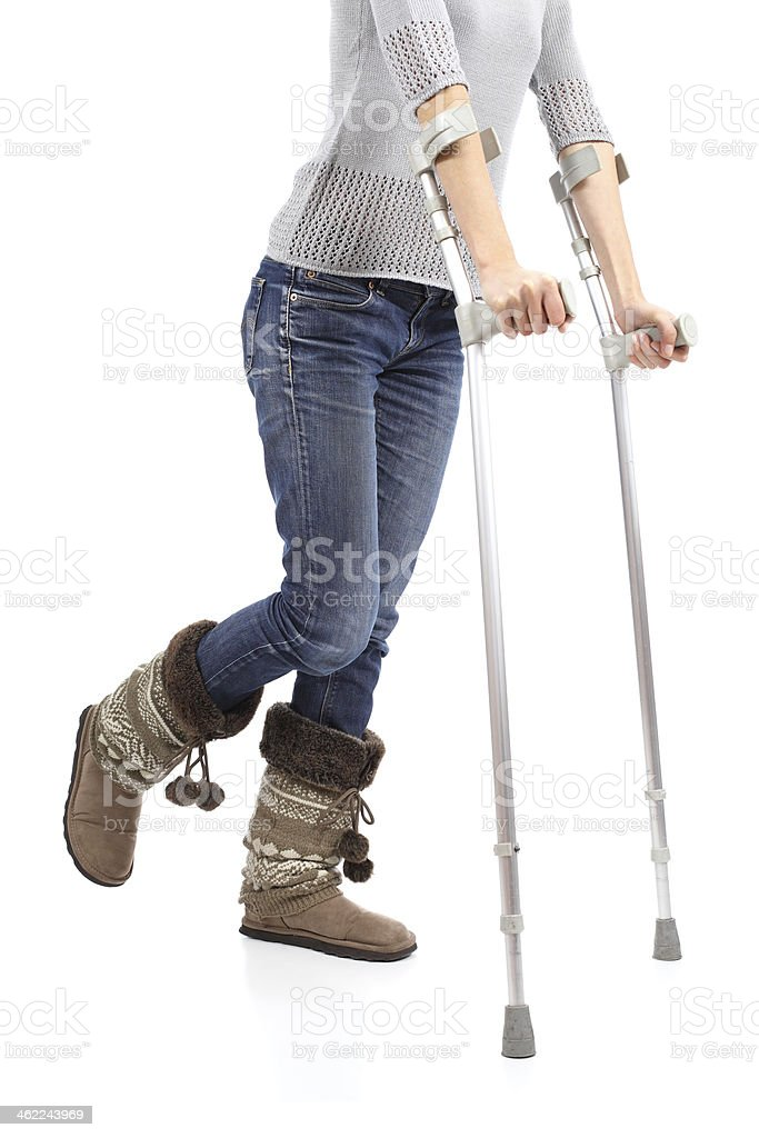 Close up of a woman walking with crutches stock photo