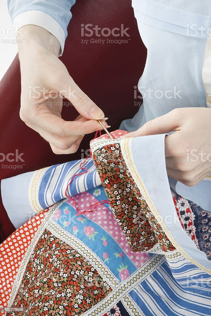 Close up of a woman's hands while stitching a quilt stock photo