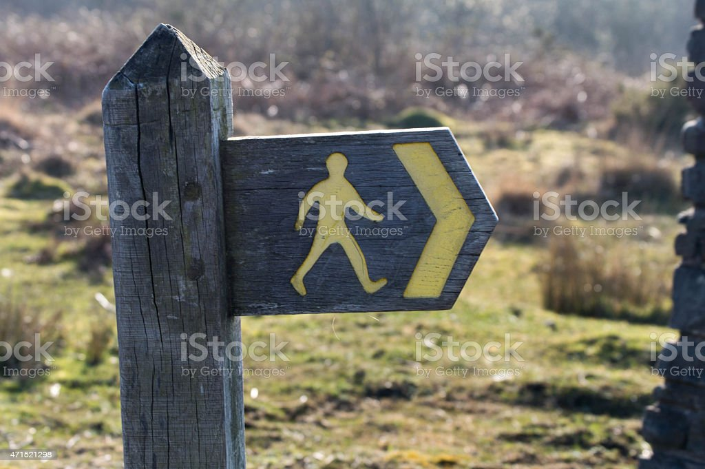 Close up of a wooden sign indicating a path way stock photo