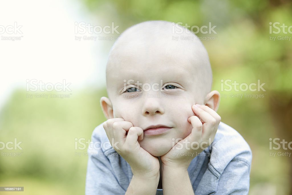 A close up of a young cancer patient daydreaming outside stock photo