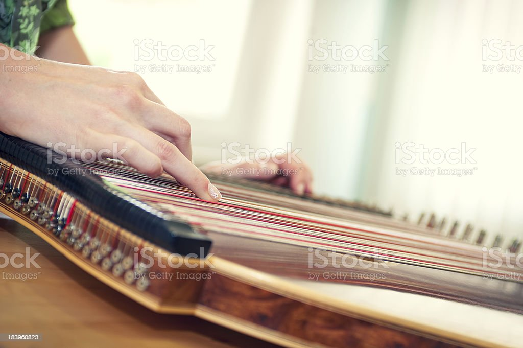 Close up of a young girl's hand playing on zither stock photo