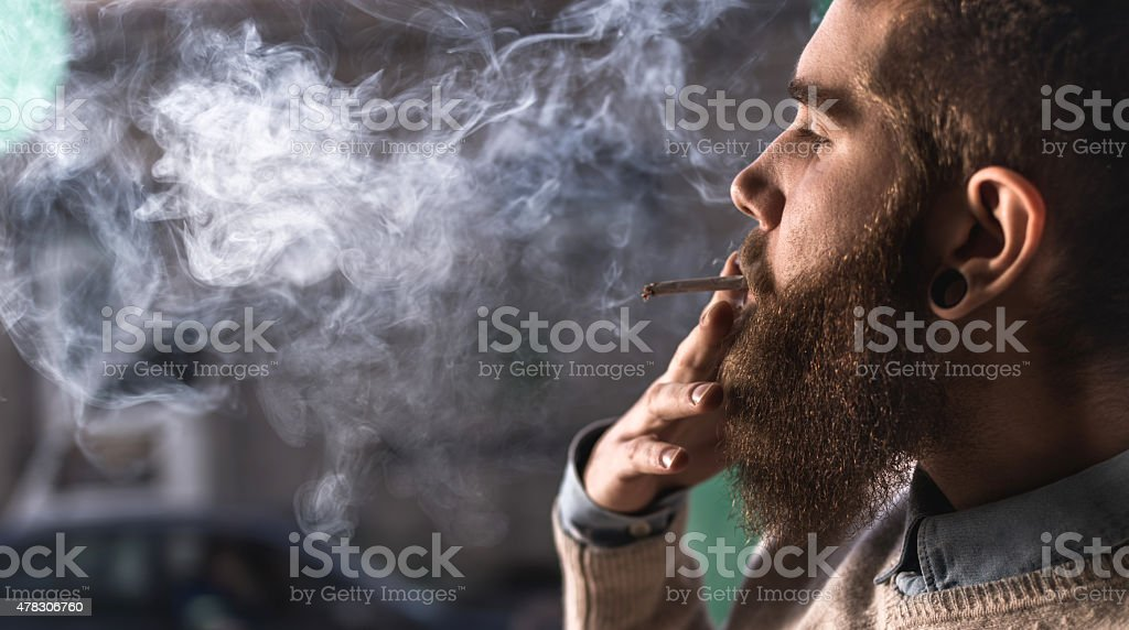 Close up of a young hipster smoking cigarette. stock photo