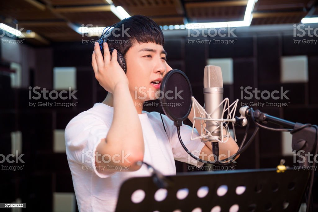 Close up of a young singer recording a track in a studio stock photo