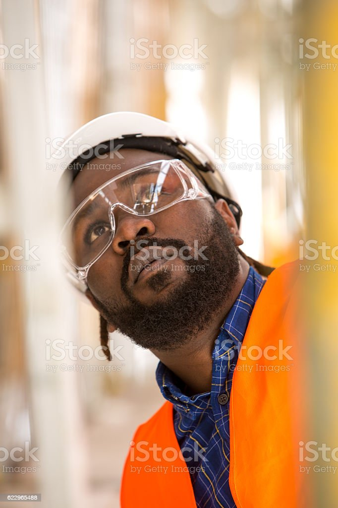 Close up of African american construction worker. Low angle view stock photo