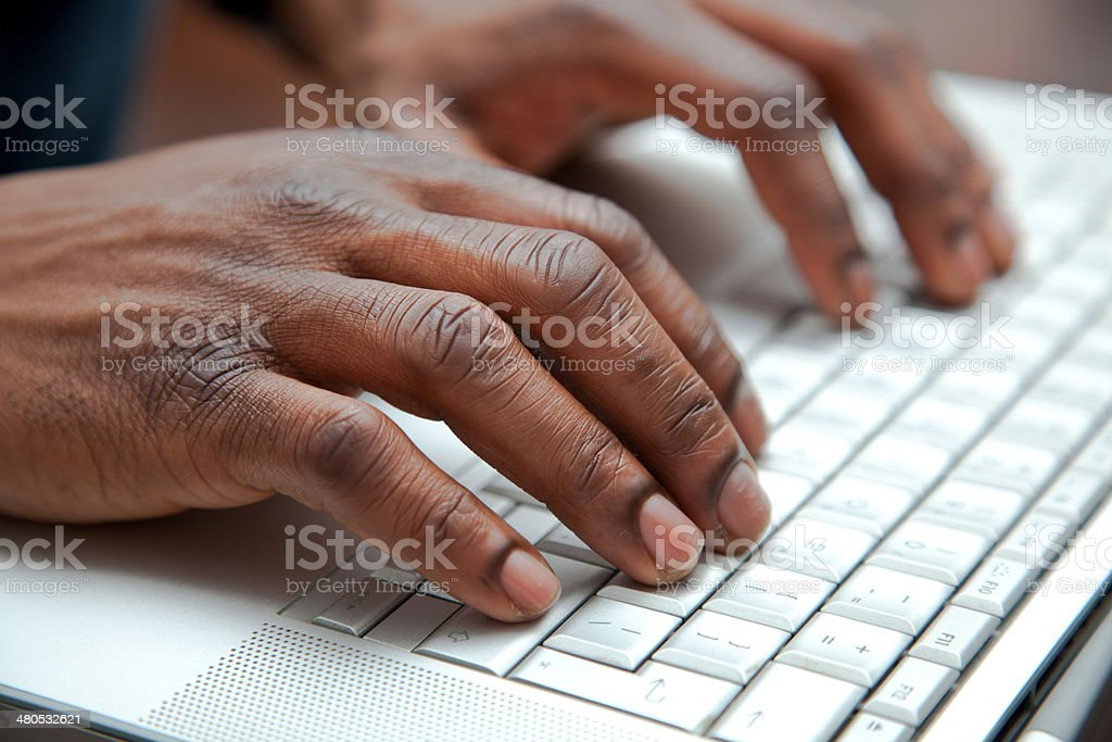 Close up of African hands on a keyboard stock photo