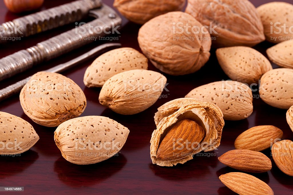Close up of almonds, one of which is half cracked royalty-free stock photo