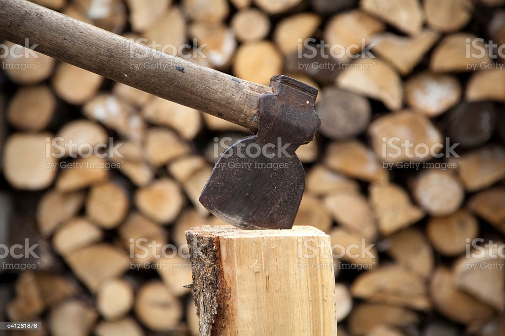 Close up of an axe with a pile of firewood stock photo