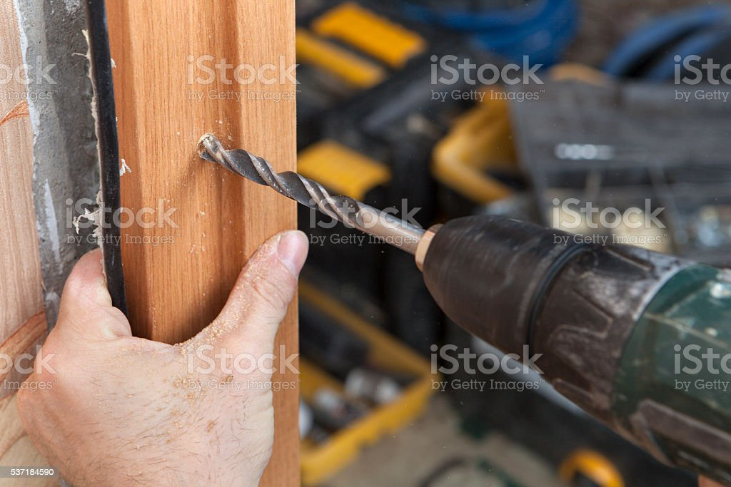 Close up of an electric drill drilled hole in doorjamb. stock photo