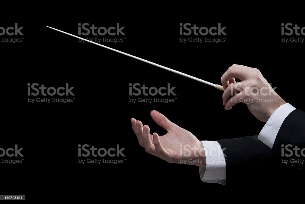Close up of an orchestra conductor's hands with a baton royalty-free stock photo